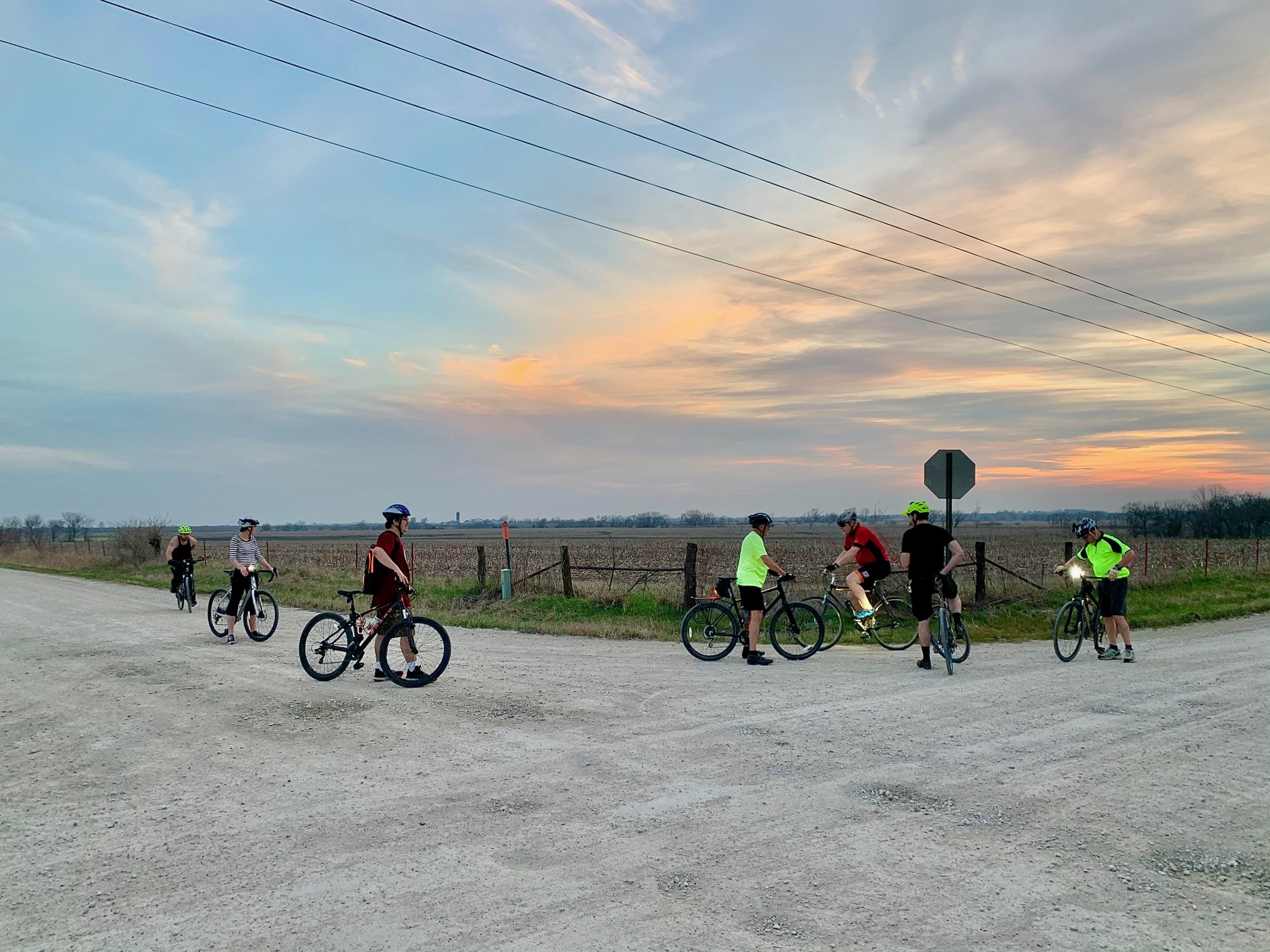 Community! Photo of a group of bicyclists resting at a crossroads of gravel roads at sunset.